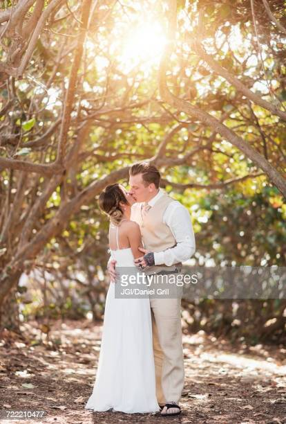 Caucasian bride and groom kissing under trees
