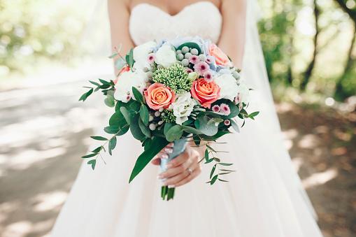 Caucasian bride holding bouquet of flowers outdoors - gettyimageskorea