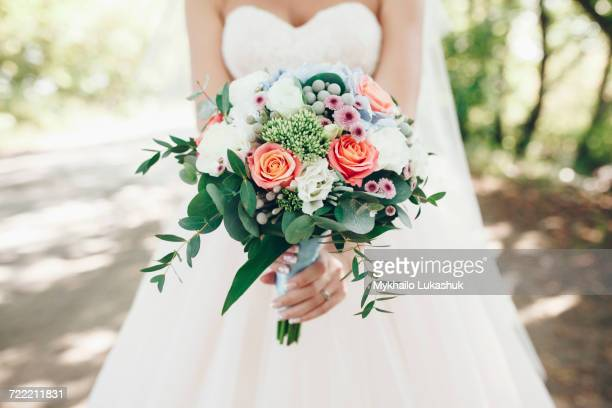 caucasian bride holding bouquet of flowers outdoors - trouwen stockfoto's en -beelden