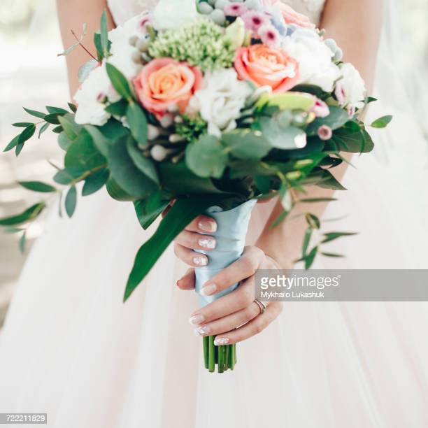 Caucasian bride holding bouquet of flowers