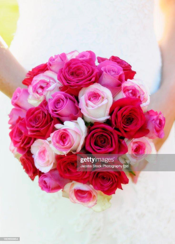 Caucasian bride holding bouquet of roses : Stock Photo
