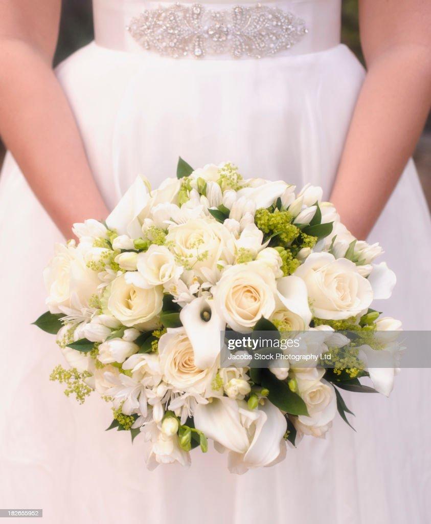 Caucasian bride holding bouquet of white flowers : Stock Photo