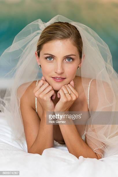 Caucasian bride in wedding veil leaning on elbows