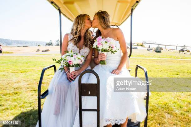 caucasian brides kissing in golf cart - civil partnership stock pictures, royalty-free photos & images