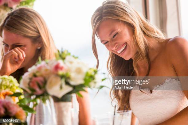 Caucasian brides laughing at table