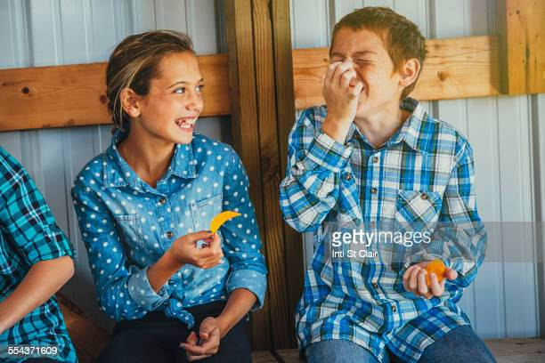 Caucasian brother and sister eating chips