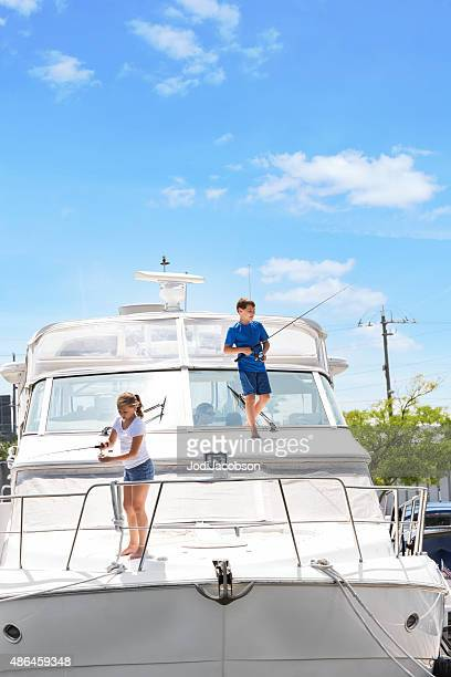 Caucasian brother and sister fishing on boat in marina