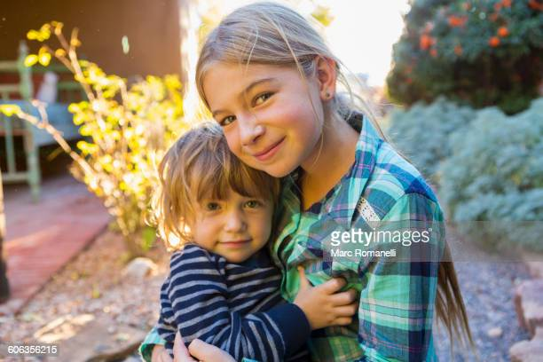Caucasian brother and sister hugging outdoors