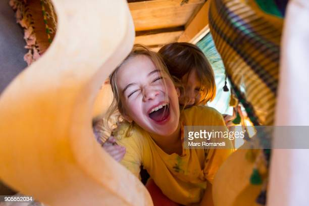 Caucasian brother and sister laughing under table