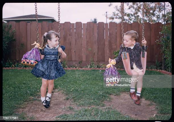 caucasian brother and sister on swings holding easter baskets - easter photos stock pictures, royalty-free photos & images