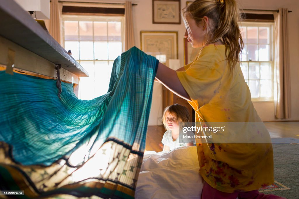 Caucasian brother and sister playing with fort under table : Stock Photo
