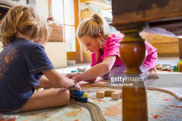 Caucasian brother and sister playing with toy race track on floor