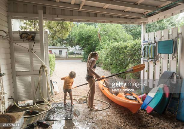Caucasian brother and sister rinsing kayak with hose