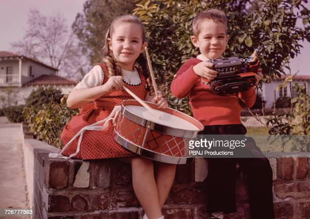 caucasian brother and sister sitting on brick wall with toys - film d'archive photos et images de collection