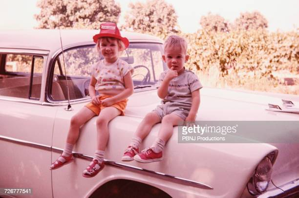 caucasian brother and sister sitting on vintage car - de archivo fotografías e imágenes de stock