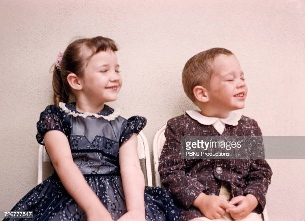 Caucasian brother and sister smiling with eyes closed