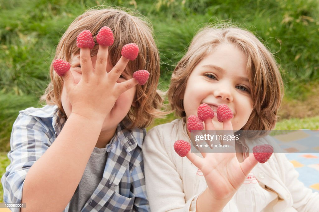 Caucasian brother and sister with raspberries on their fingers : Stock Photo