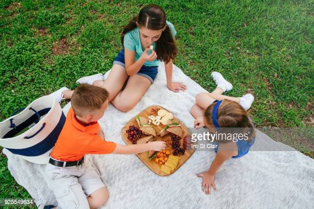 Caucasian brother and sisters eating snacks on picnic blanket