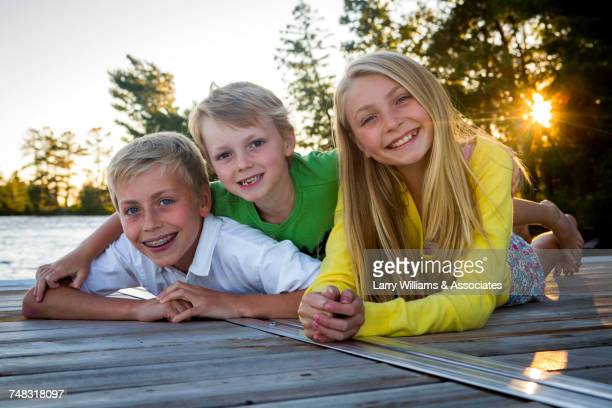 Caucasian brothers and sister laying on dock at lake