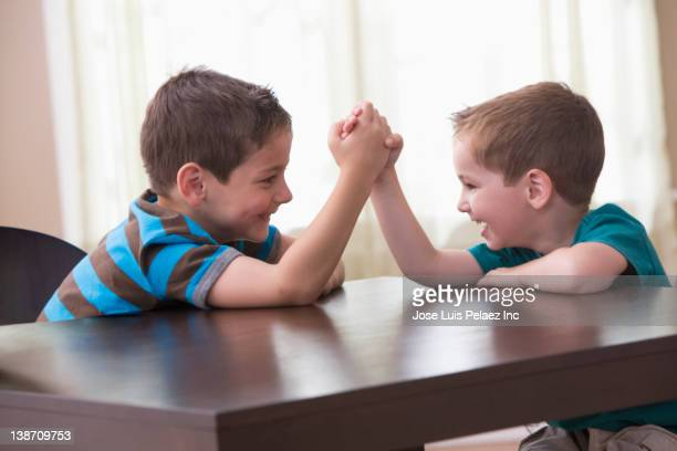 Caucasian brothers arm wrestling