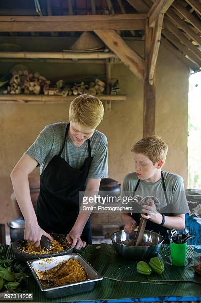Caucasian brothers cooking in outdoor kitchen