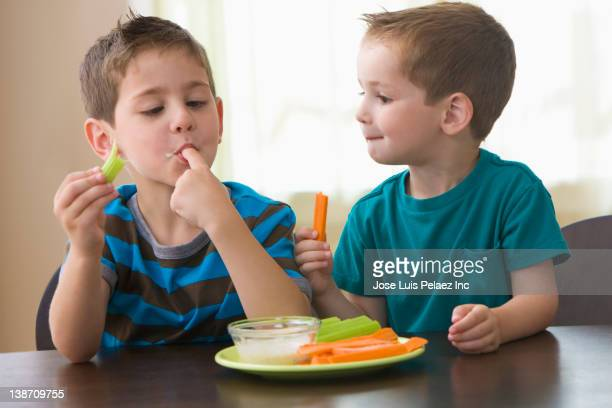 Caucasian brothers eating vegetables and dip