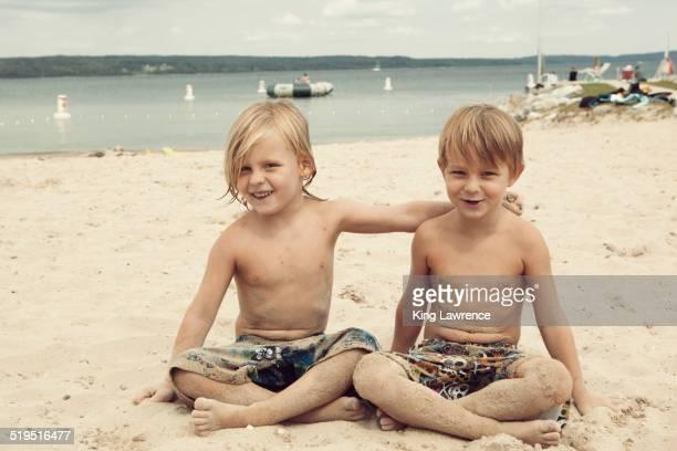 Caucasian brothers hugging on beach
