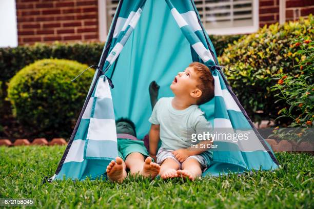 Caucasian brothers in backyard teepee