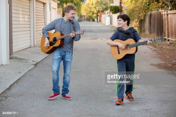 Caucasian brothers playing guitars in alley