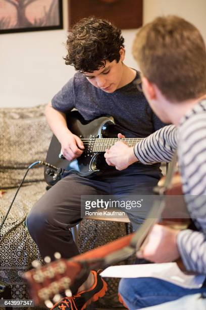 Caucasian brothers playing guitars in living room