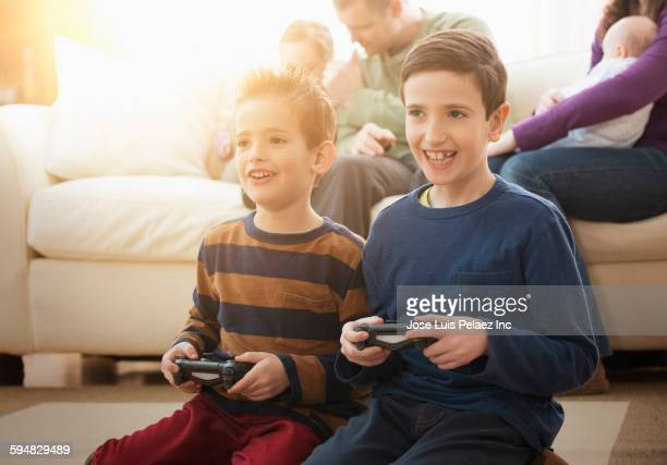 Caucasian brothers playing video games