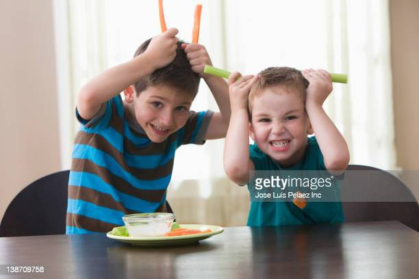 Caucasian brothers playing with vegetables