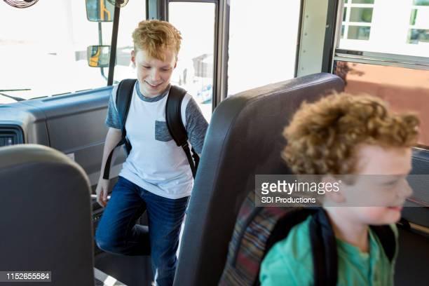 i fratelli caucasici s'alzano nello scuolabus - indipendenza foto e immagini stock