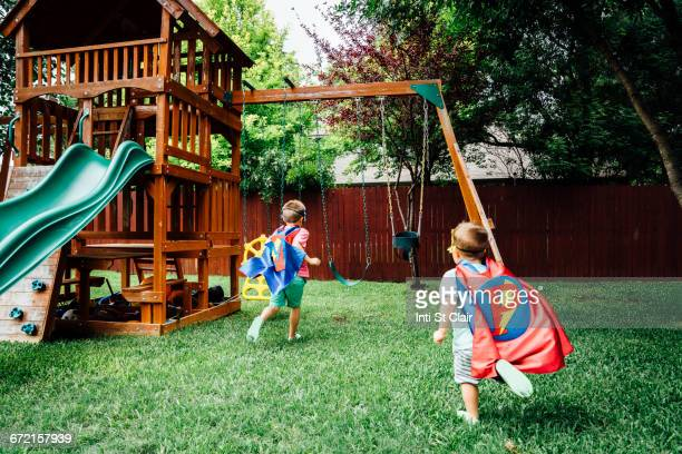 Caucasian brothers wearing superhero costumes in backyard