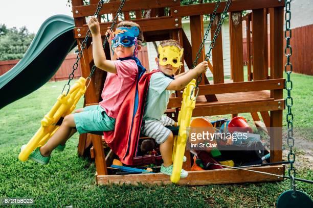 Caucasian brothers wearing superhero costumes on swing