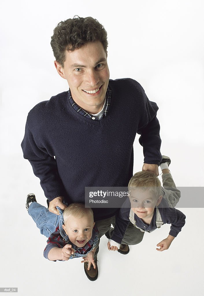 caucasian brown haired single father holds two young sons by their pants laughing : Foto de stock