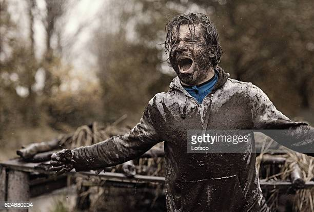 Caucasian brunette handsome man at obstacle during a mud run