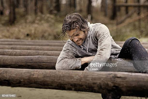 Caucasian brunette handsome man crawling over obstacle during mud run