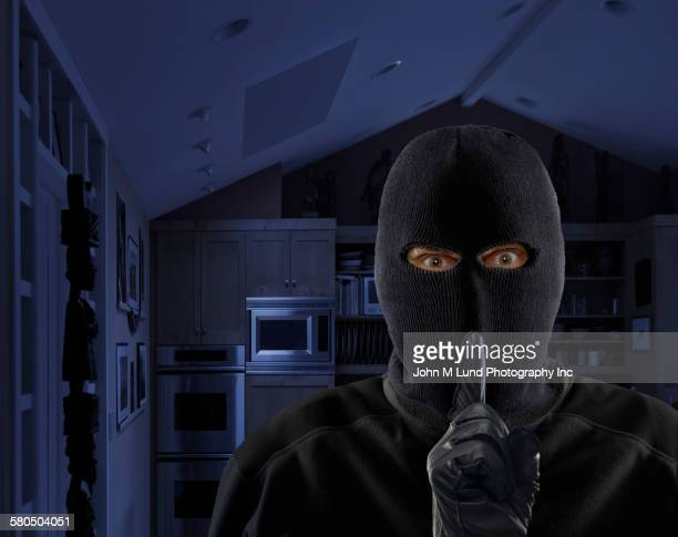 Caucasian burglar gesturing quiet in house at night