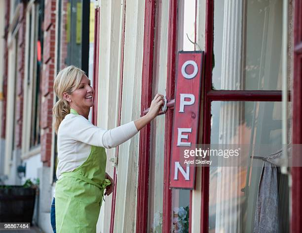 Caucasian business owner cleaning store windows