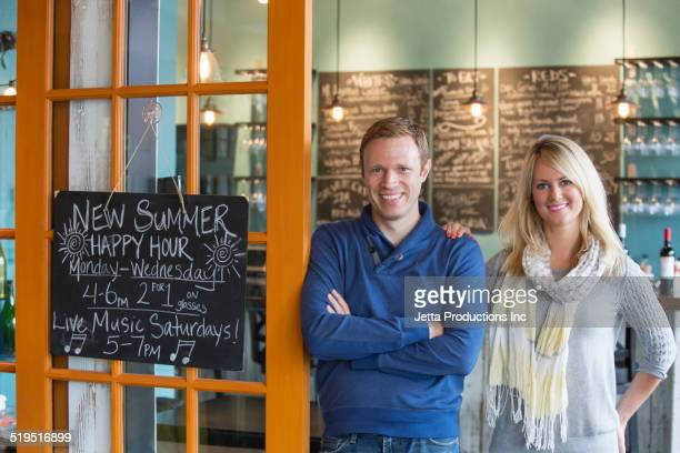 Caucasian business owners smiling in wine bar