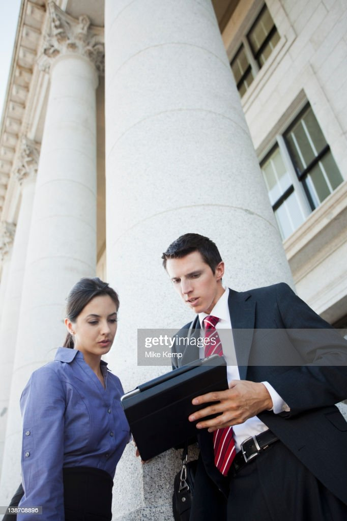 Caucasian business people looking at digital tablet : Stock Photo
