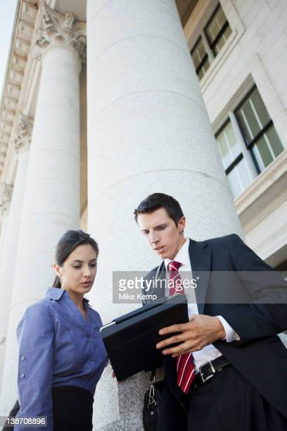 Caucasian business people looking at digital tablet