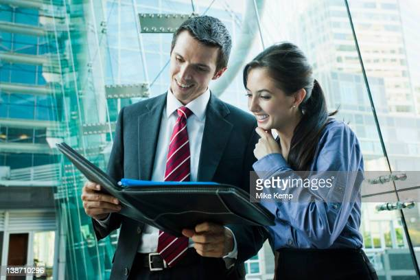 Caucasian business people looking at notebook together