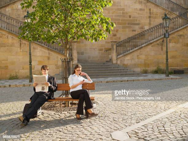 Caucasian business people relaxing on bench in city