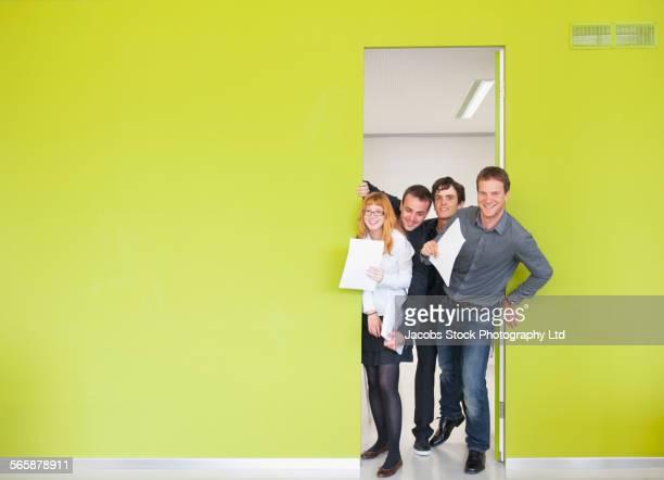 Caucasian business people smiling in office doorway