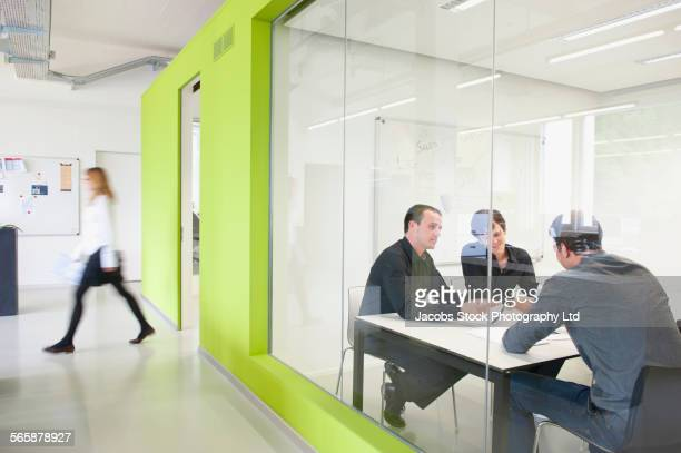 Caucasian business people talking in meeting in busy office