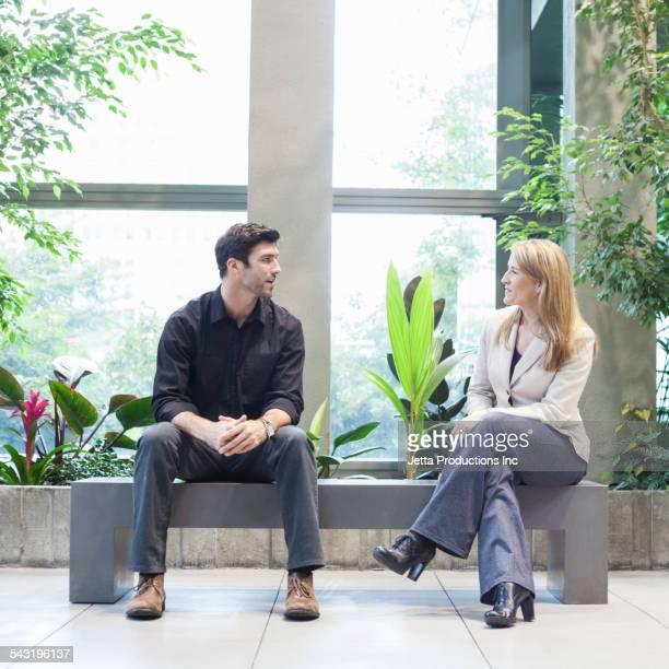 Caucasian business people talking in office lobby