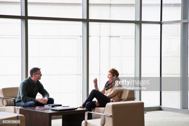 Caucasian business people talking in office lounge