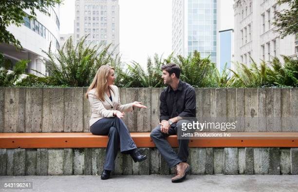 caucasian business people talking on bench outdoors - sitzen stock-fotos und bilder